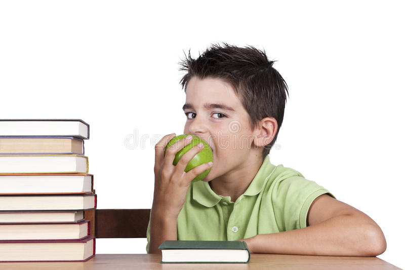 Muchacho en escritorio de la escuela que come la fruta fotografía de archivo libre de regalías