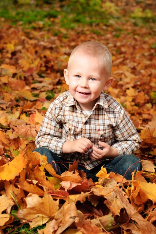 Muchacho en hojas de otoño imagenes de archivo