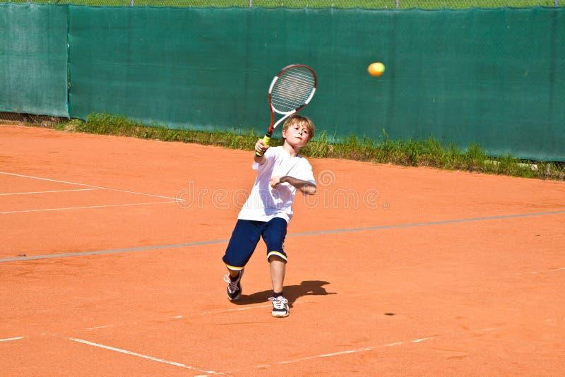 Muchacho en la lección de tenis foto de archivo