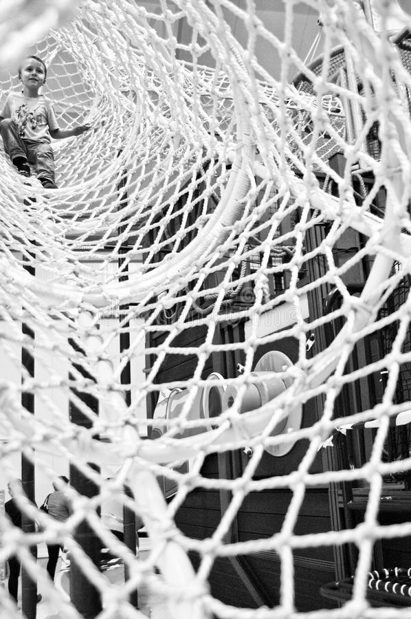 Muchacho en la manga neta de la instalación que sube del parque de atracciones fotografía de archivo
