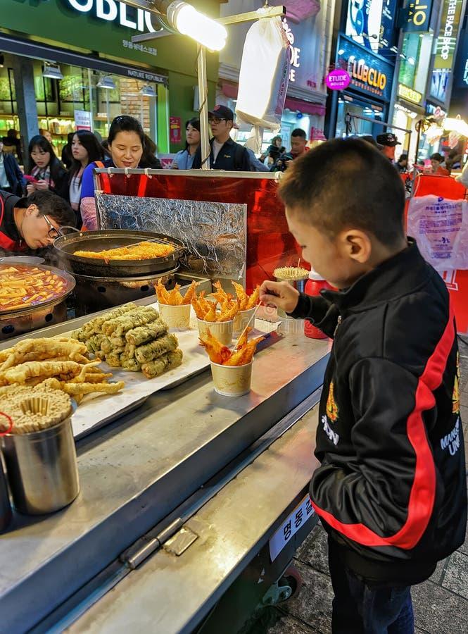 Muchacho en la parada de los mariscos en el mercado callejero abierto Seul de Myeongdong imagen de archivo libre de regalías