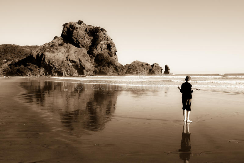 Muchacho en la playa de la arena del negro del océano fotos de archivo libres de regalías