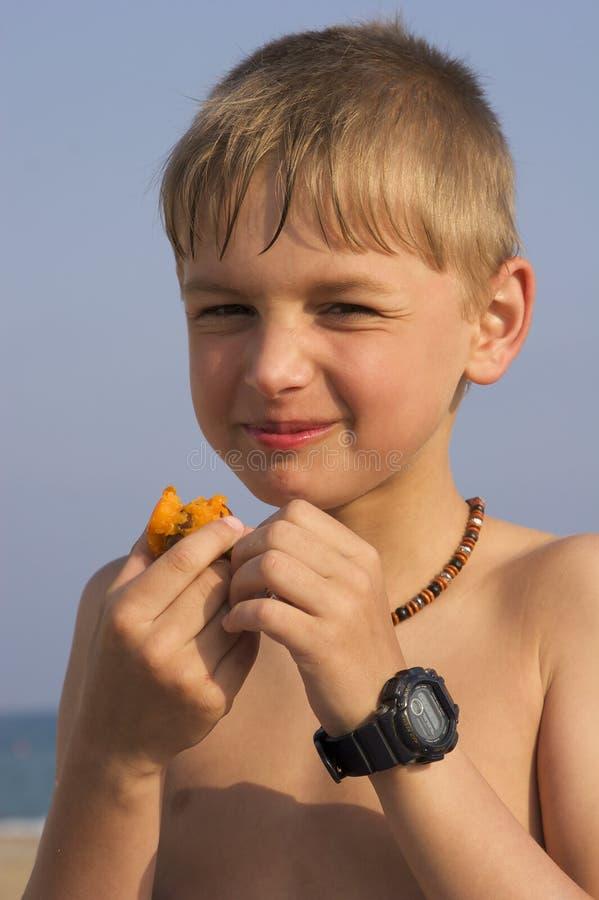 Muchacho en la playa que come el ciruelo imagen de archivo libre de regalías
