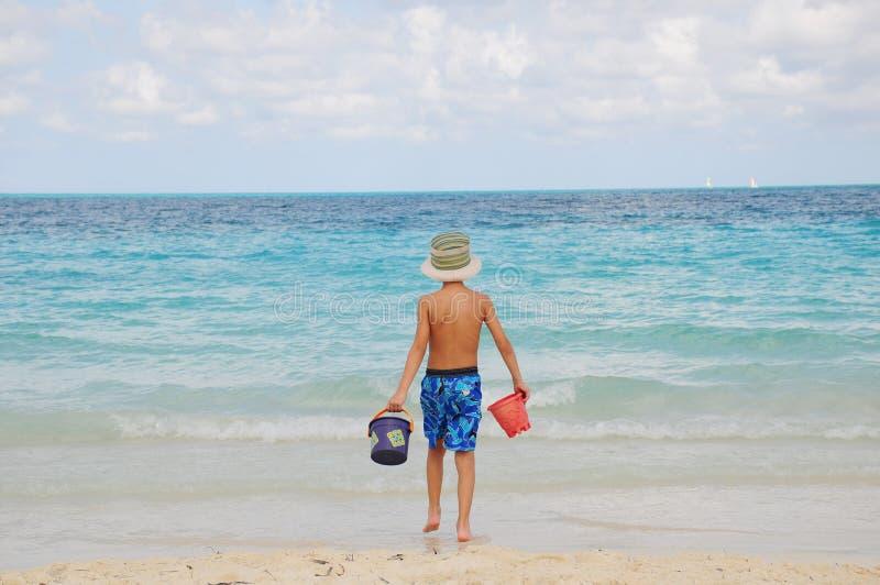 Muchacho en la playa que juega en la arena imagen de archivo