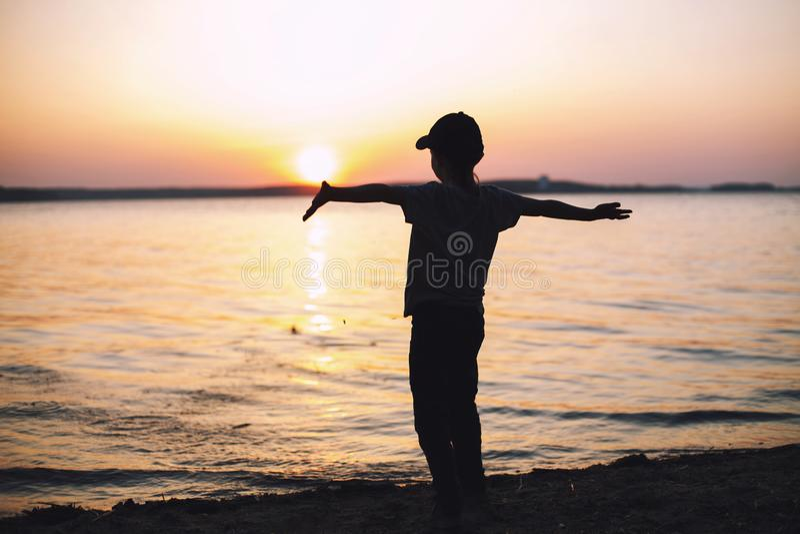 Muchacho en la puesta del sol en la playa y aumentada sus manos para arriba foto de archivo