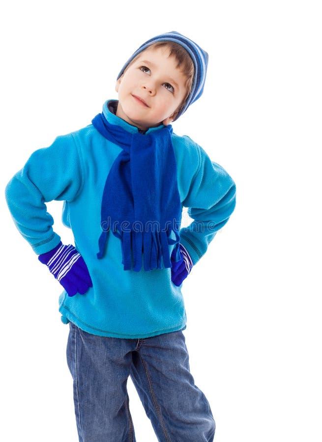 Muchacho en la ropa del invierno que mira con la pregunta foto de archivo
