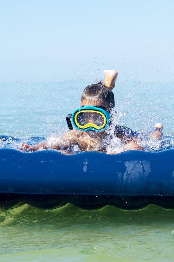Muchacho en nadada de la máscara de la natación en el mar con el colchón inflable imagen de archivo