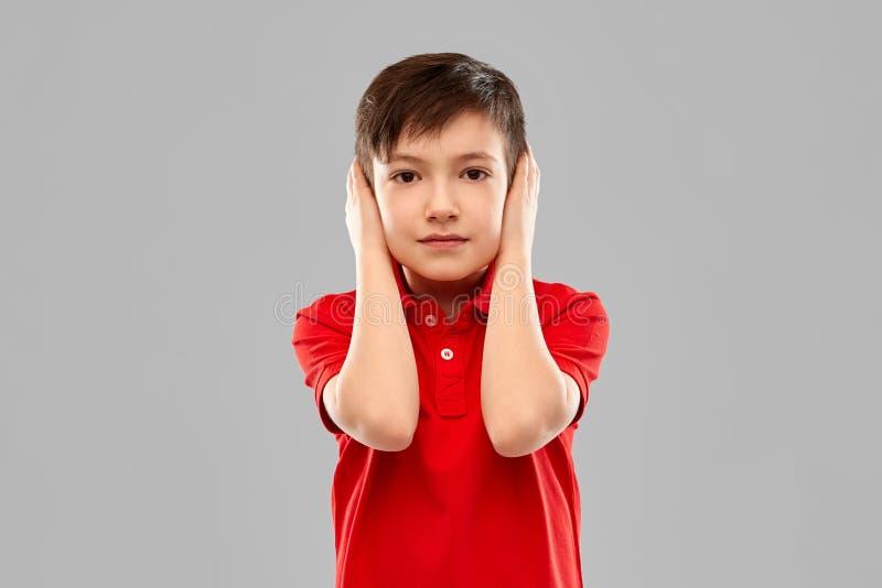 Muchacho en oídos de cierre de la camiseta roja por las manos fotos de archivo