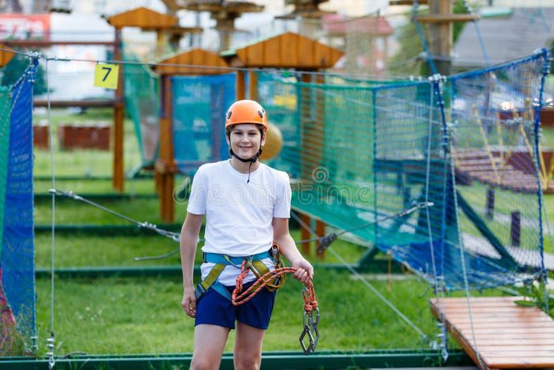 Muchacho en parque de la aventura del bosque Niño en casco anaranjado y subidas blancas de la camiseta en alto rastro de la cuerd imagen de archivo