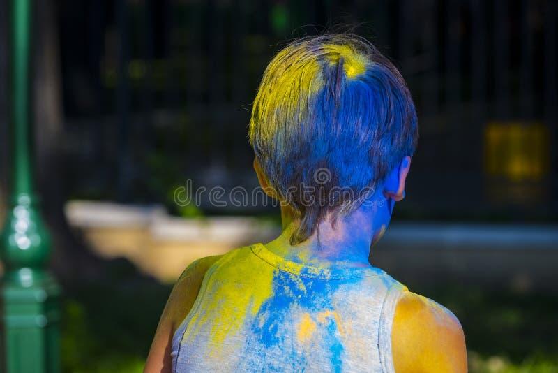 muchacho en pintura azul y amarilla en la celebración del día de fiesta Holi imagen de archivo libre de regalías