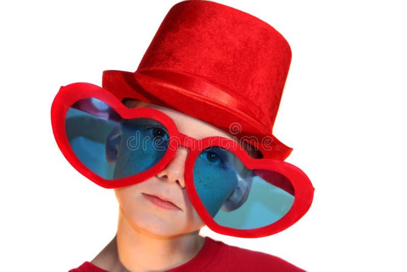 Muchacho en Red Hat y los vidrios del corazón horizontales imágenes de archivo libres de regalías
