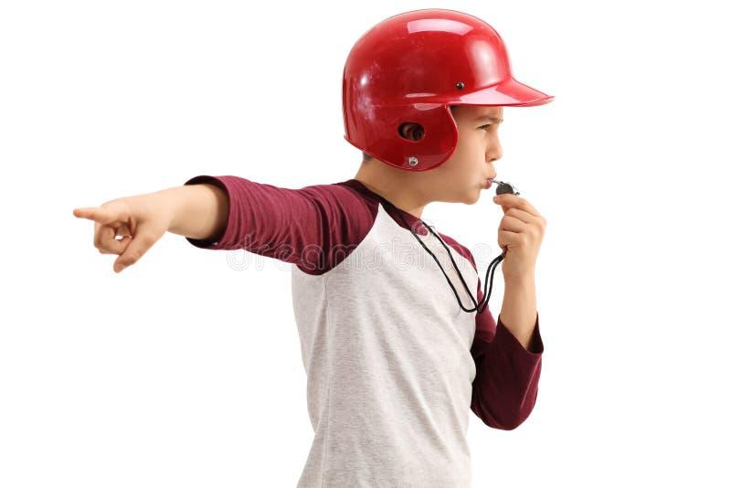 Muchacho en silbido que sopla y señalar de la ropa de deportes con su mano imagen de archivo libre de regalías