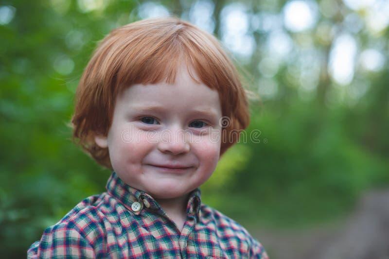Muchacho en sonrisas de la camisa de tela escocesa foto de archivo