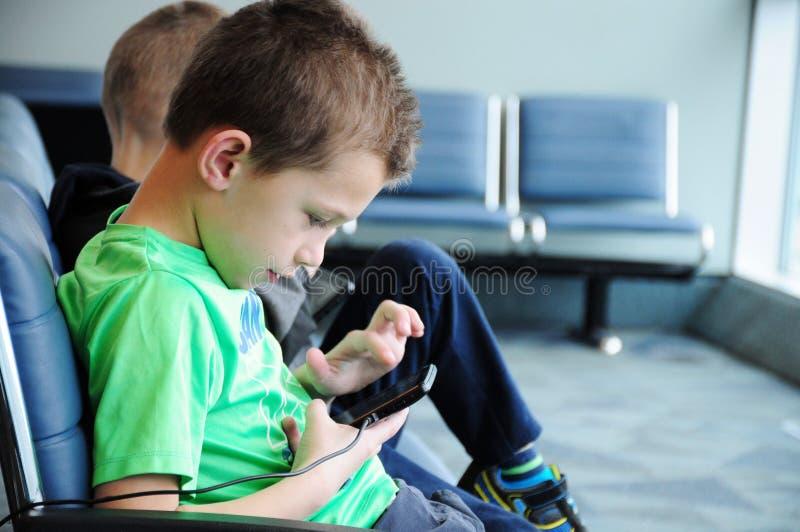 Muchacho en su tableta en el aeropuerto fotos de archivo libres de regalías