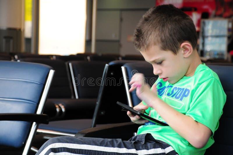Muchacho en su tableta en el aeropuerto imagenes de archivo