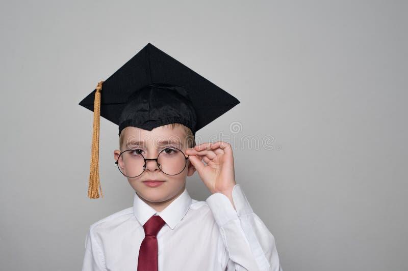 Muchacho en un casquillo académico cuadrado y una camisa blanca que corrigen los vidrios Fondo blanco Concepto de la escuela foto de archivo libre de regalías