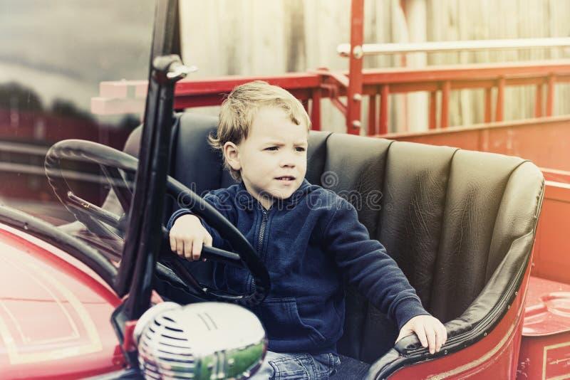 Muchacho en un coche de bomberos del vintage - retro fotos de archivo