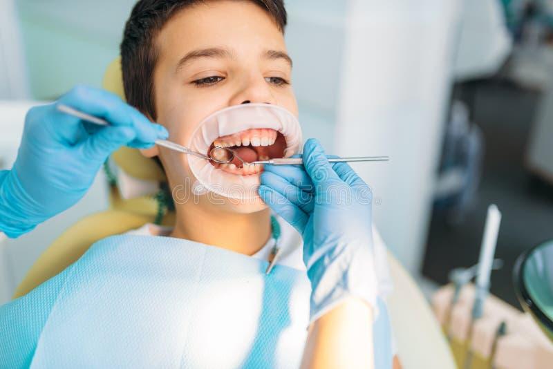 Muchacho en un gabinete dental, retiro de la carie foto de archivo