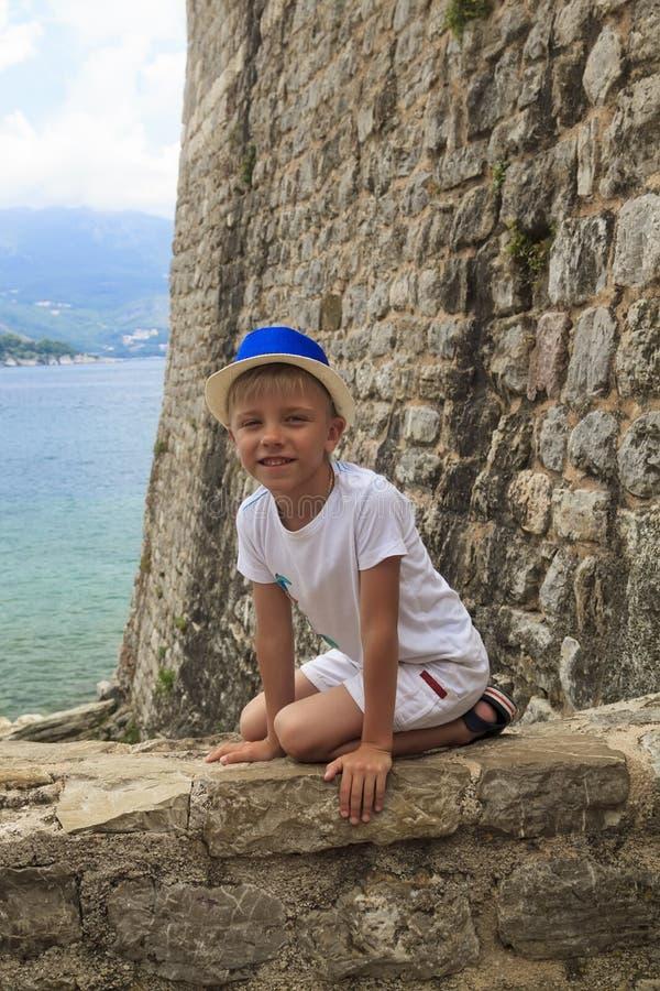 muchacho en un sombrero azul que se sienta en el parapeto de la fortaleza antigua de fotos de archivo