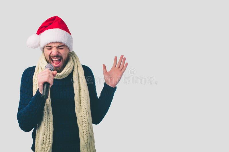 Muchacho en un sombrero de la Navidad que oscila hacia fuera Imagen de un hombre hermoso que canta al micrófono, aislada en luz e foto de archivo