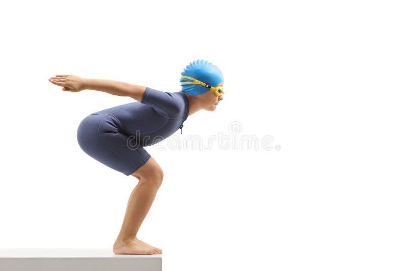 Muchacho en un wetsuit que consigue listo para saltar para una nadada imágenes de archivo libres de regalías