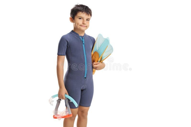 Muchacho en un wetsuit que sostiene una máscara que se zambulle y aletas fotos de archivo