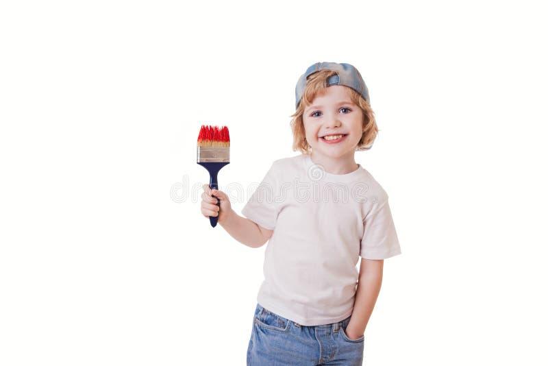Muchacho en una camiseta blanca con una brocha en sus manos, pinturas o fotografía de archivo libre de regalías