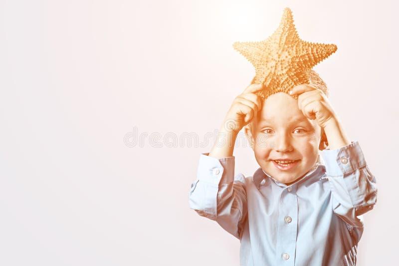 Muchacho en una camiseta ligera que sostiene una estrella de mar en un fondo blanco fotos de archivo
