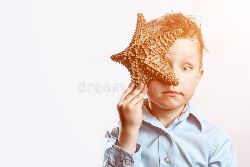 Muchacho en una camiseta ligera que sostiene una estrella de mar en un fondo blanco fotos de archivo libres de regalías