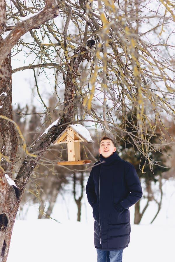 muchacho en una chaqueta del invierno entre los árboles del invierno foto de archivo