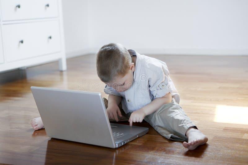 Muchacho en una computadora portátil que se sienta en el suelo descalzo fotos de archivo