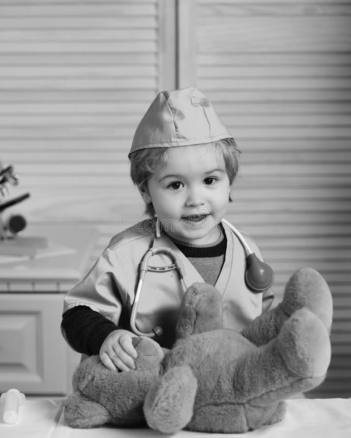 Muchacho en uniforme y estetoscopio quirúrgicos en cuello en fondo de madera Embrome en juegos de la capa del doctor con el oso d imagen de archivo