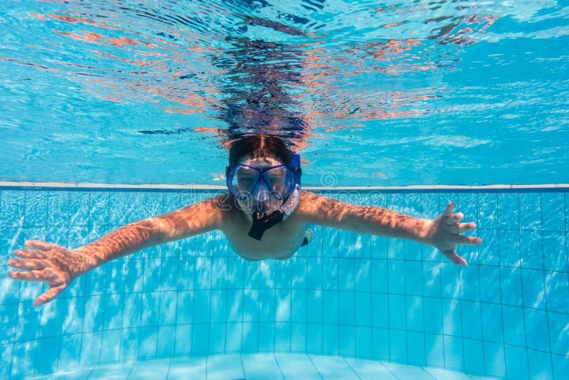 Muchacho en zambullida de la máscara en piscina foto de archivo libre de regalías