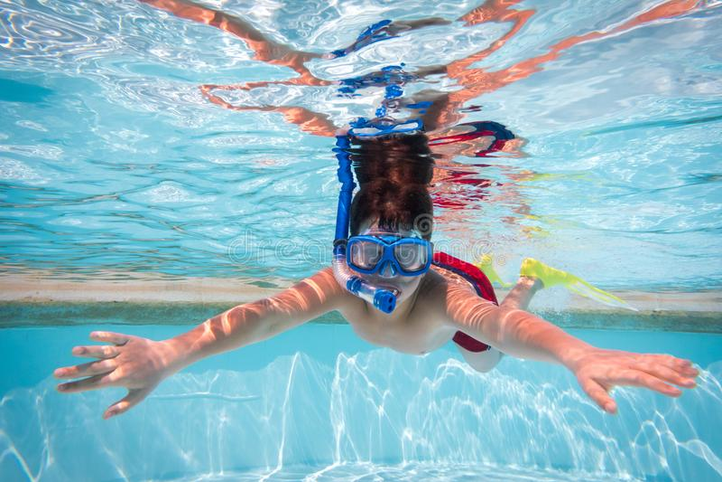 Muchacho en zambullida de la máscara en piscina fotografía de archivo libre de regalías