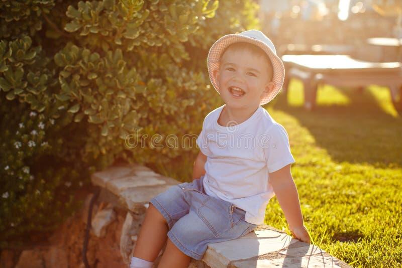 Muchacho encantador en un sombrero en un fondo de palmeras en la puesta del sol adentro foto de archivo libre de regalías