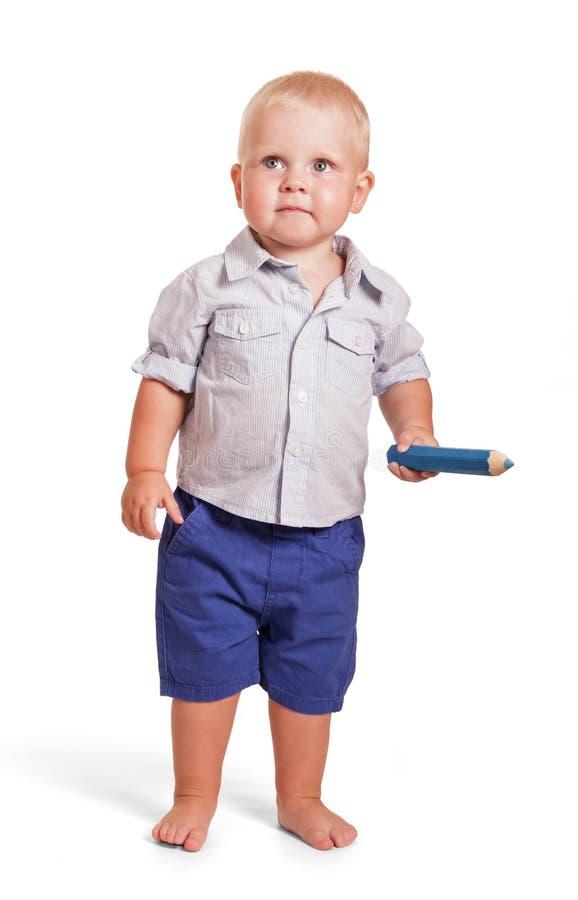 Muchacho encantador que coloca y que sostiene el lápiz grande aislado en blanco imágenes de archivo libres de regalías
