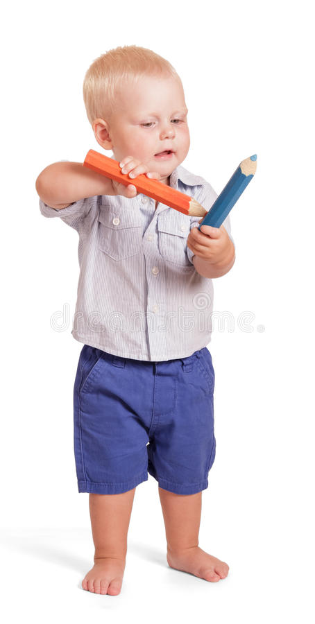 Muchacho encantador que coloca y que sostiene el lápiz grande dos aislado imagen de archivo libre de regalías