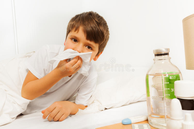 Muchacho enfermo del niño que sopla su nariz con una servilleta fotos de archivo libres de regalías