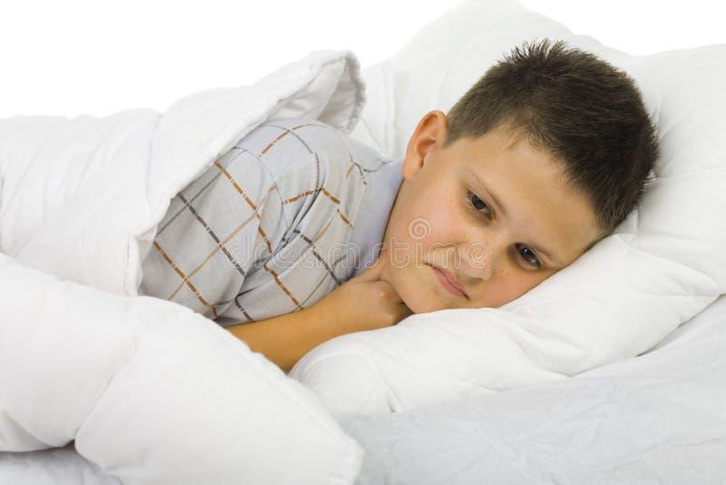 Muchacho enfermo en cama imagenes de archivo