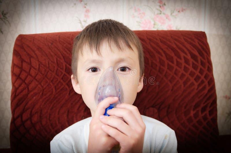 Muchacho enfermo en la máscara del nebulizador que hace la inhalación, el procedimiento respiratorio por pulmonía o la tos para e imagen de archivo