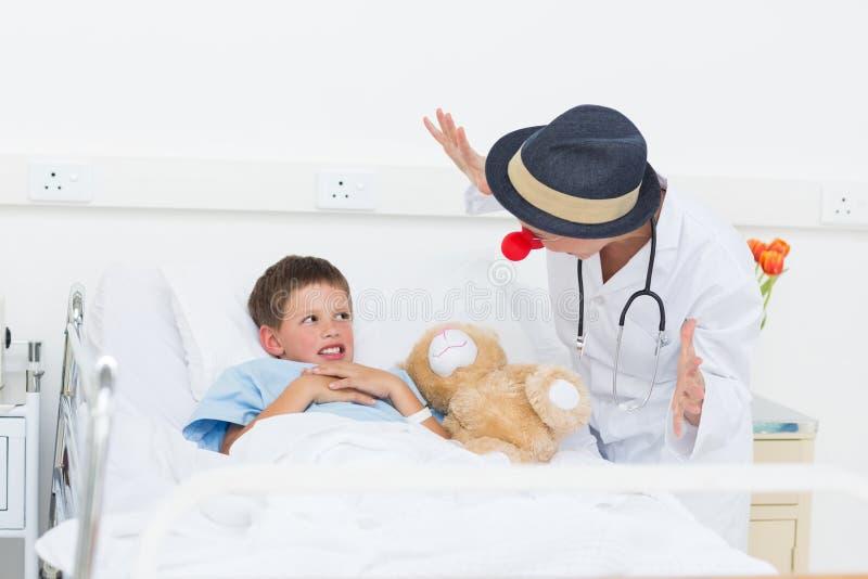 Muchacho enfermo entretenido del doctor en cama de hospital foto de archivo libre de regalías
