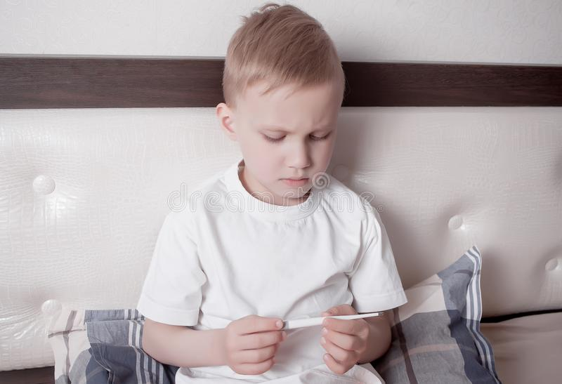 Muchacho enfermo que se sienta en cama y que mira el termómetro digital El muchacho enfermo está midiendo temperatura del cuerpo  imagen de archivo