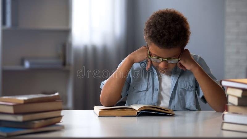 Muchacho enfocado que aprende la literatura, libro de lectura en la biblioteca, preparándose para el examen fotos de archivo libres de regalías