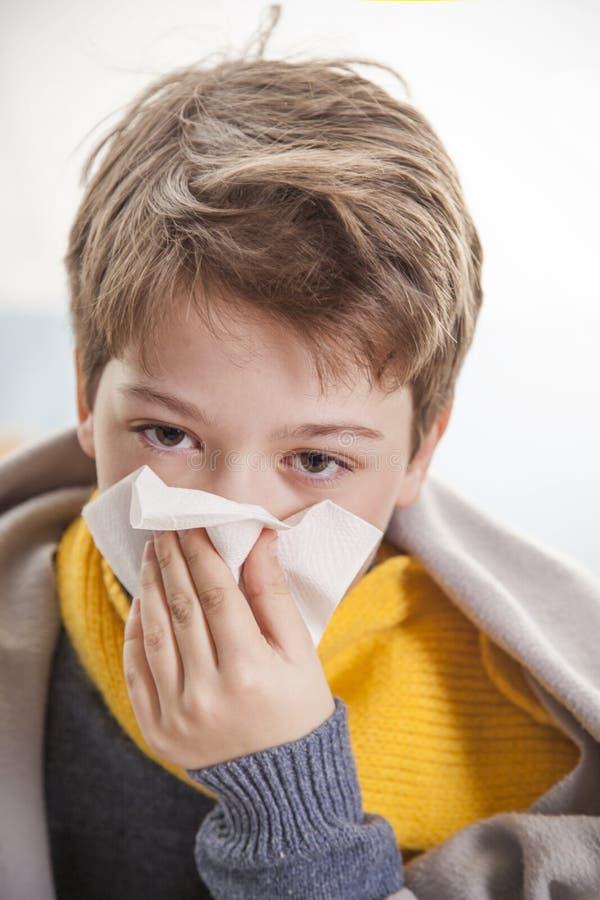 Muchacho enfriarse y soplar su nariz en casa imagen de archivo