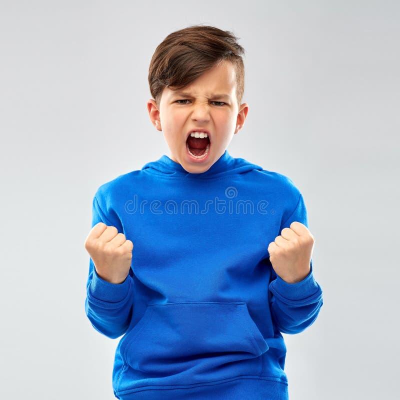 Muchacho enojado en sudadera con capucha azul que celebra éxito foto de archivo libre de regalías