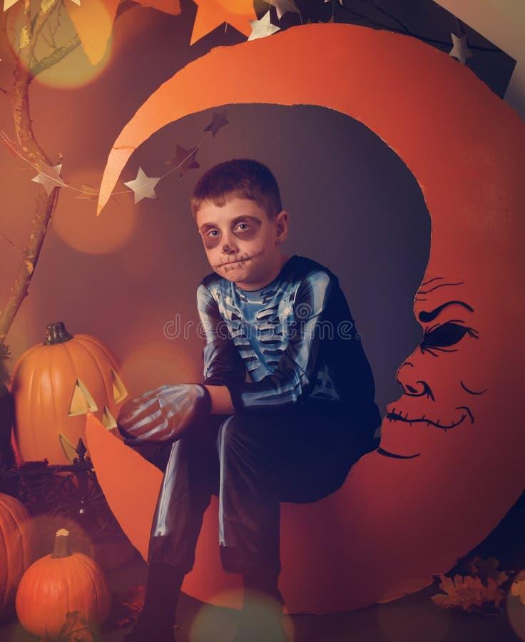 Muchacho esquelético en traje en cara de luna anaranjada imagen de archivo