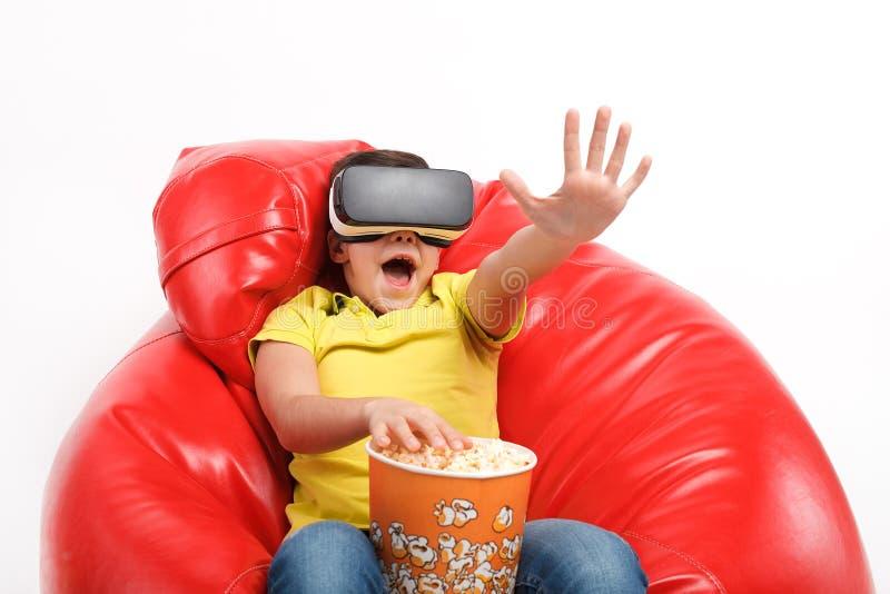 Muchacho expresivo con palomitas y gafas de VR imagenes de archivo
