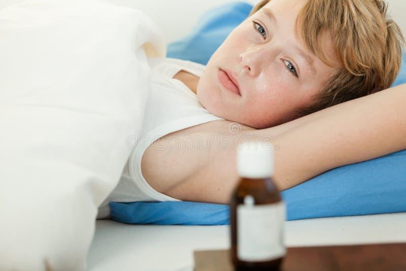 Muchacho febril en cama al lado de la botella de la medicina foto de archivo