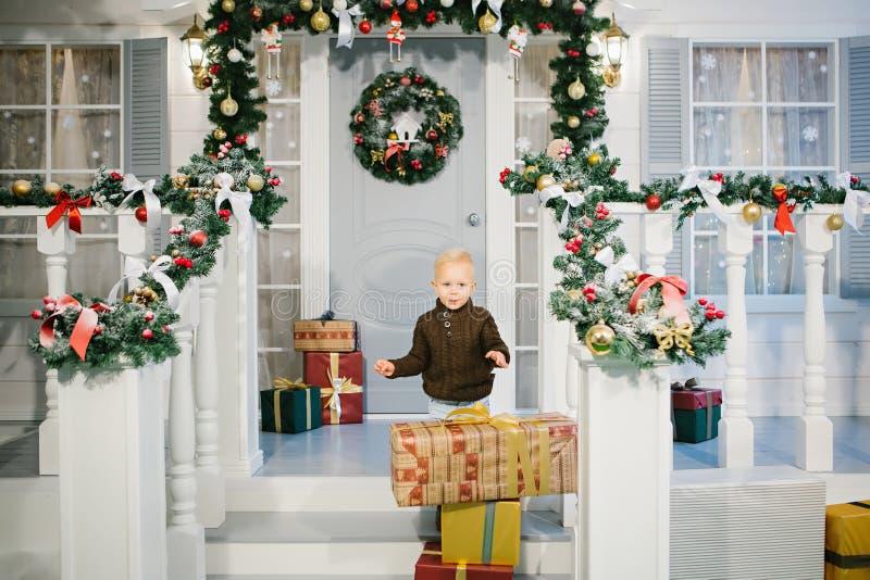 Muchacho feliz cerca de los regalos de la Navidad fotografía de archivo libre de regalías
