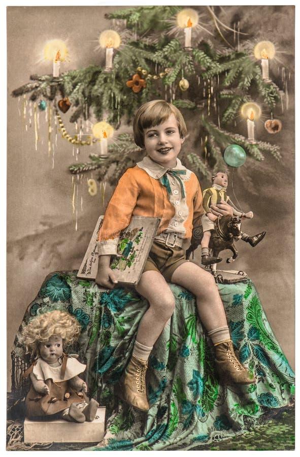 Muchacho feliz con el árbol de navidad, los regalos y los juguetes del vintage fotos de archivo